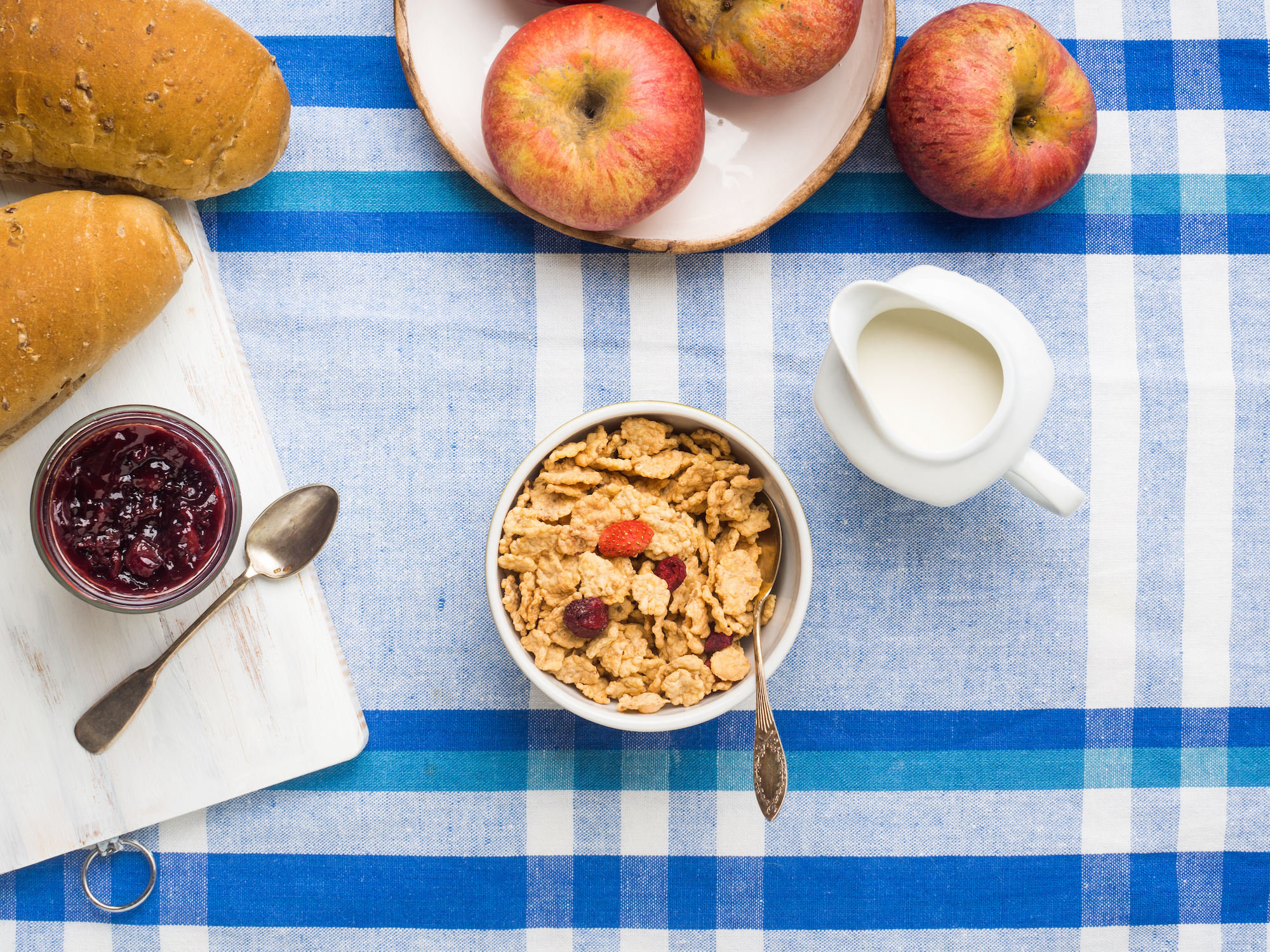 Home breakfast with cereals, milk, fruit and bread served on blue and white table cloth.