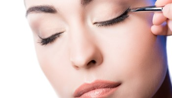 Makeup artist applying eyeliner arrows on face. hand of woman using makeup brush