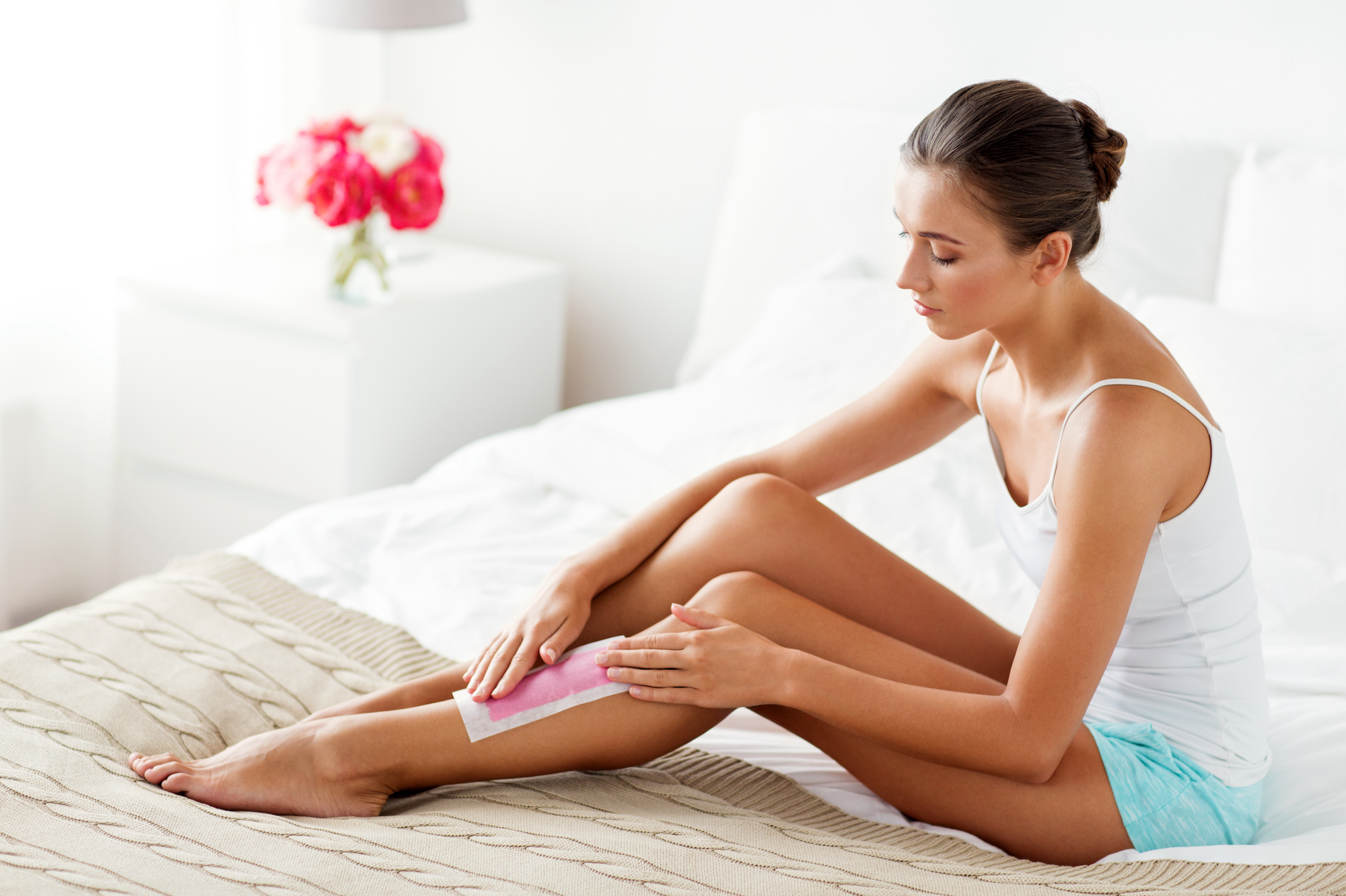 beauty, depilation, epilation, hair removal and people concept - beautiful woman applying depilatory wax strip to her leg skin at home bedroom