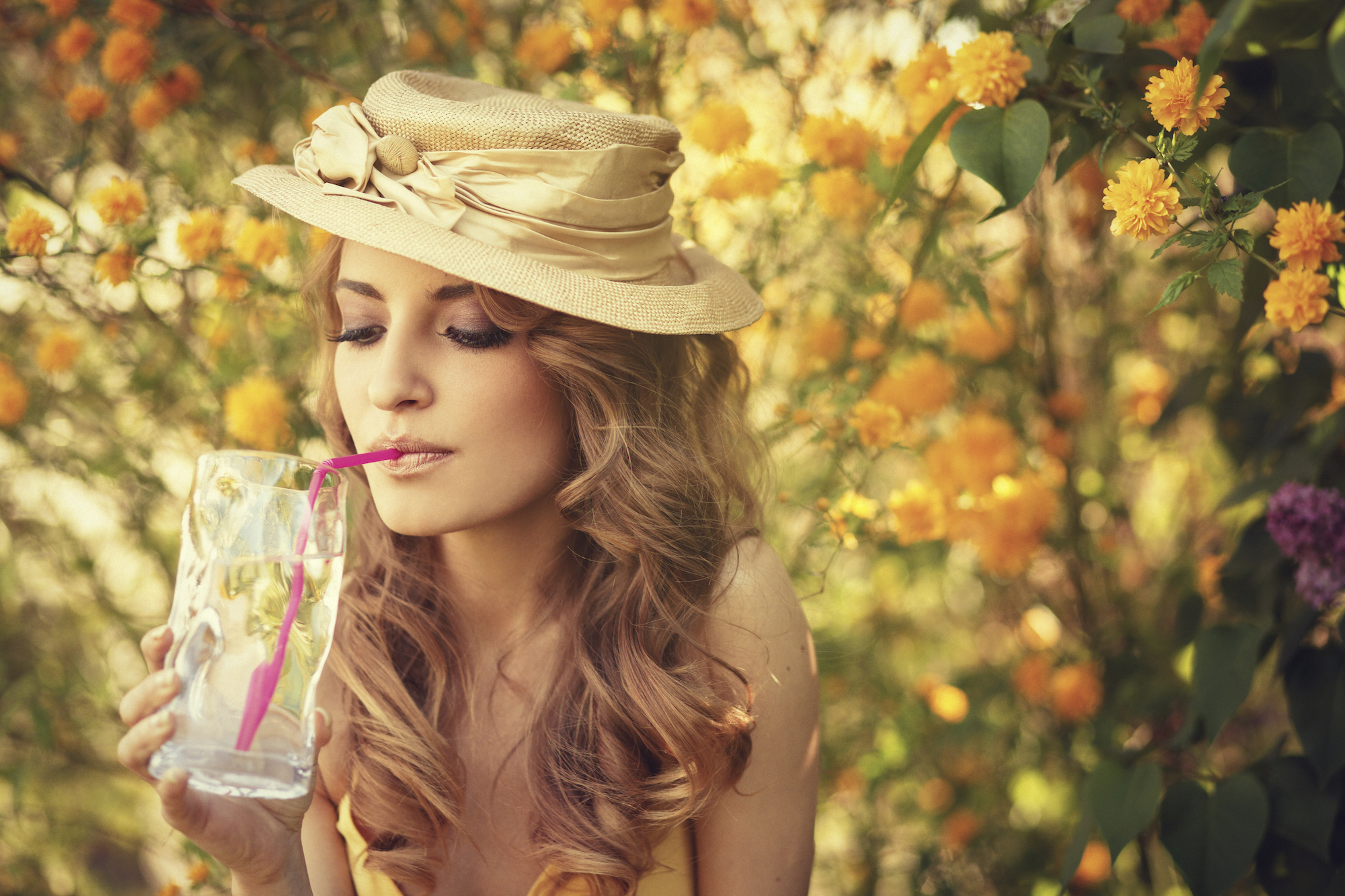 Girl with a hat drinking a glass of water with a straw