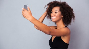 Smiling afro american woman making selfie photo
