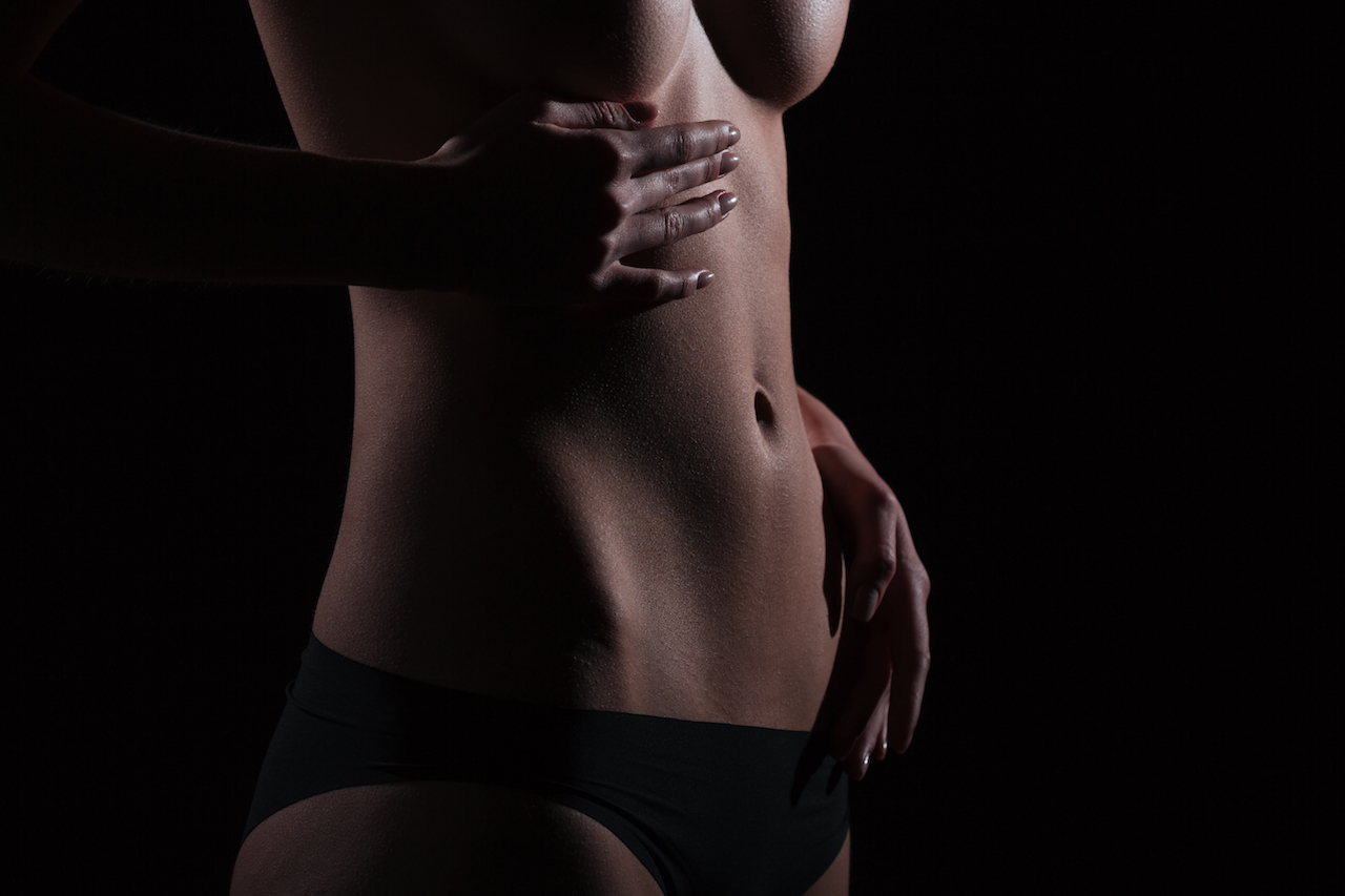 Closeup portrait of a sexy female body over black background