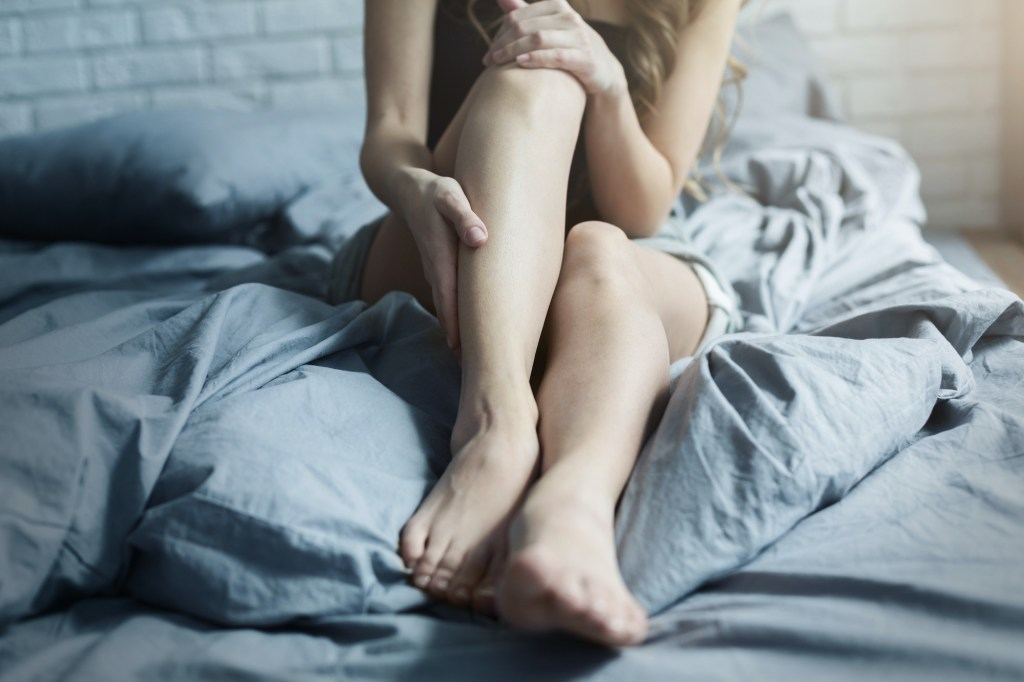 Female legs in bed, closeup. After laser hair removal beauty treatment.