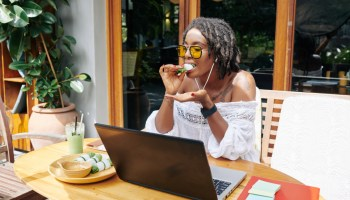 African young woman in sunglasses sitting at wooden table in front of laptop and eating during her work in outdoor cafe
