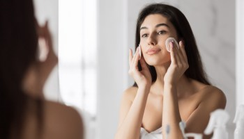 Young cute woman remove makeup , cleaning face with cotton pads looking in mirror at bathroom. Pure healthy skin concept