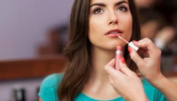 Applying lip-gloss to the lips of beautiful woman