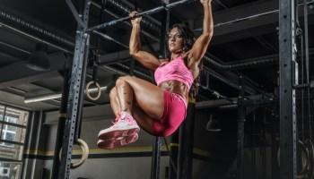 Athletic brunette female in pink sportswear doing abs exercises on horizontal bar.