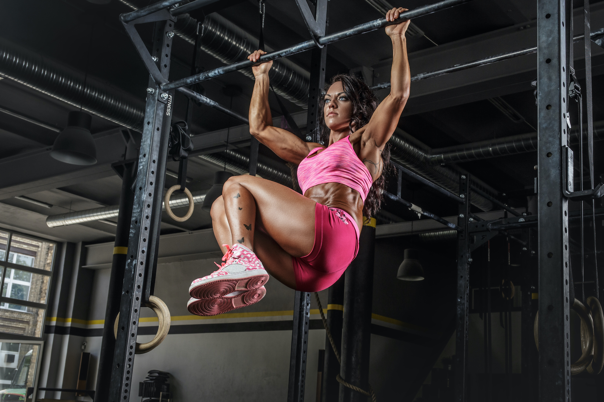 Athletic brunette female in pink sportswear doing abs exercises on horizontal bar.