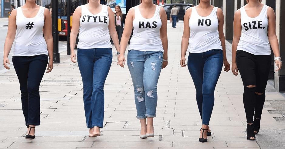 five women walking on the sidewalk
