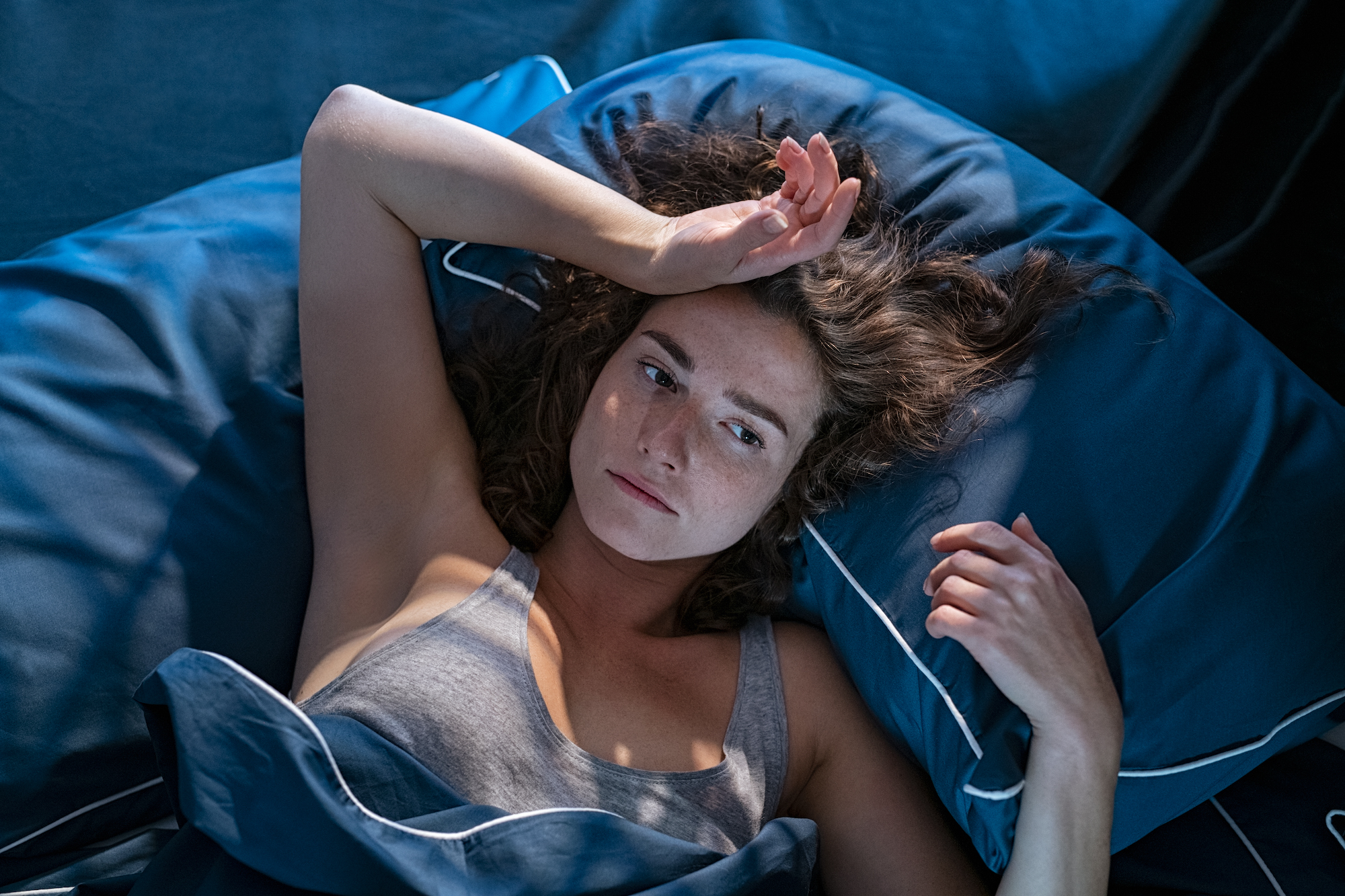 Young stressed woman lying on bed late at night suffering from insomnia, sleep apnea or stress. Top view of depressed girl lying bed with dark pillow and blue blanket late at night. High angle view of awake girl in the middle of the night.