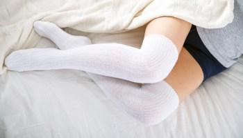 Female legs in white knee socks lying in bed at home