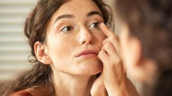 Woman applying contact lens in bathroom
