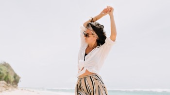 Elegant attractive woman with hands up on beach. Smiling happy multicultural female model in white summer outfit enjoying serene ocean nature during travel holidays vacation outdoors.