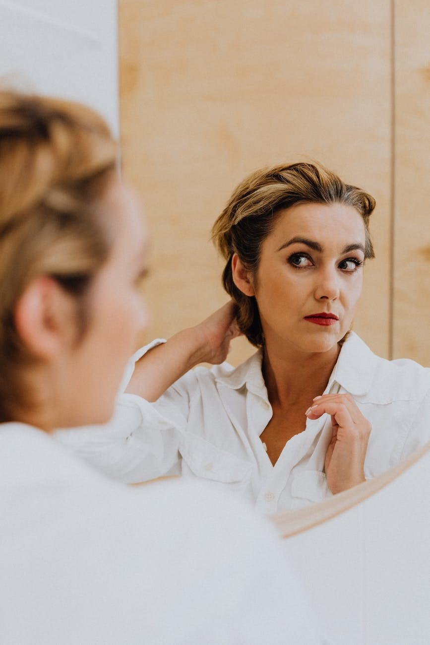 woman in white long sleeve shirt in front of the mirror