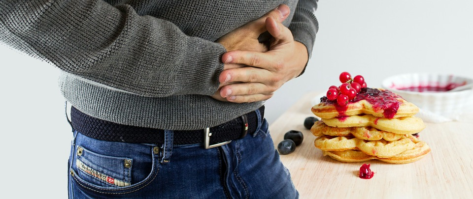 unhealthy-eating-habits -man- holding- stomach