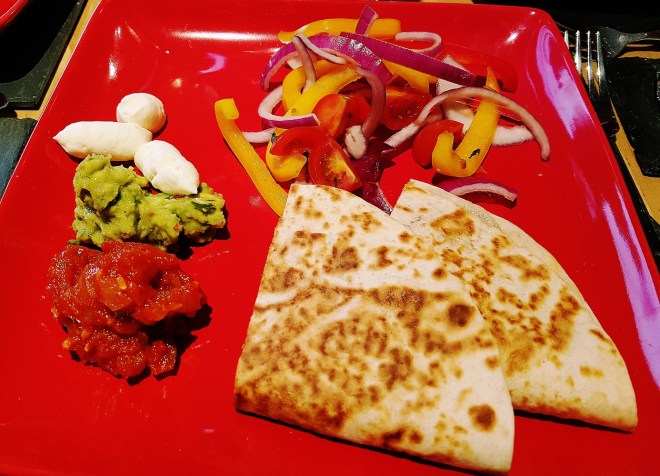 Quesadillas with salad, sour cream and homemade salsa and guacamole for a dinner party