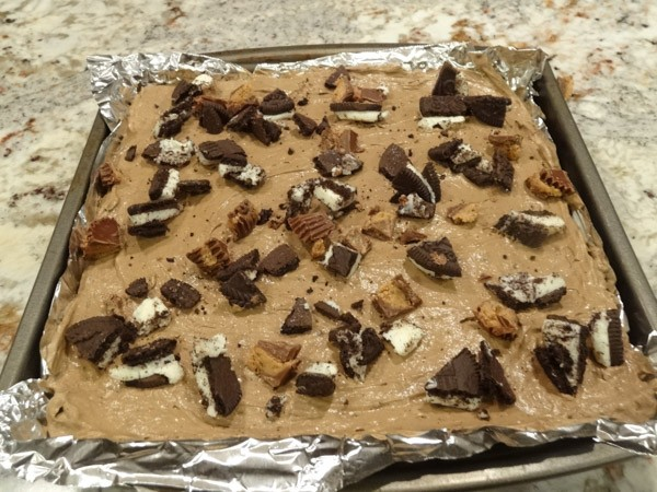 Peanut Butter cups and Oreo cookies sprinkled on top of pudding layer