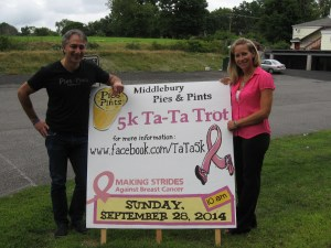 Theo Anastasiadis, left, and Karen Nocera, right, stand by the sign advertising the Pies & Pints 5K Ta-Ta Trot, which will be held Sept. 28. Not shown is Pies & Pints co-owner Christos Gogas. (Marjorie Needham photo)