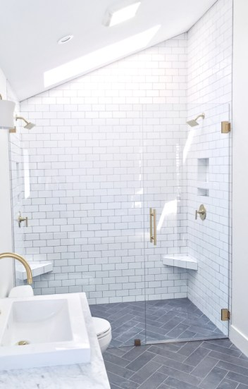 Master bathroom with white subway tile, gray herringbone floors, brass fixtures, and floating wood vanity by Beebout Design
