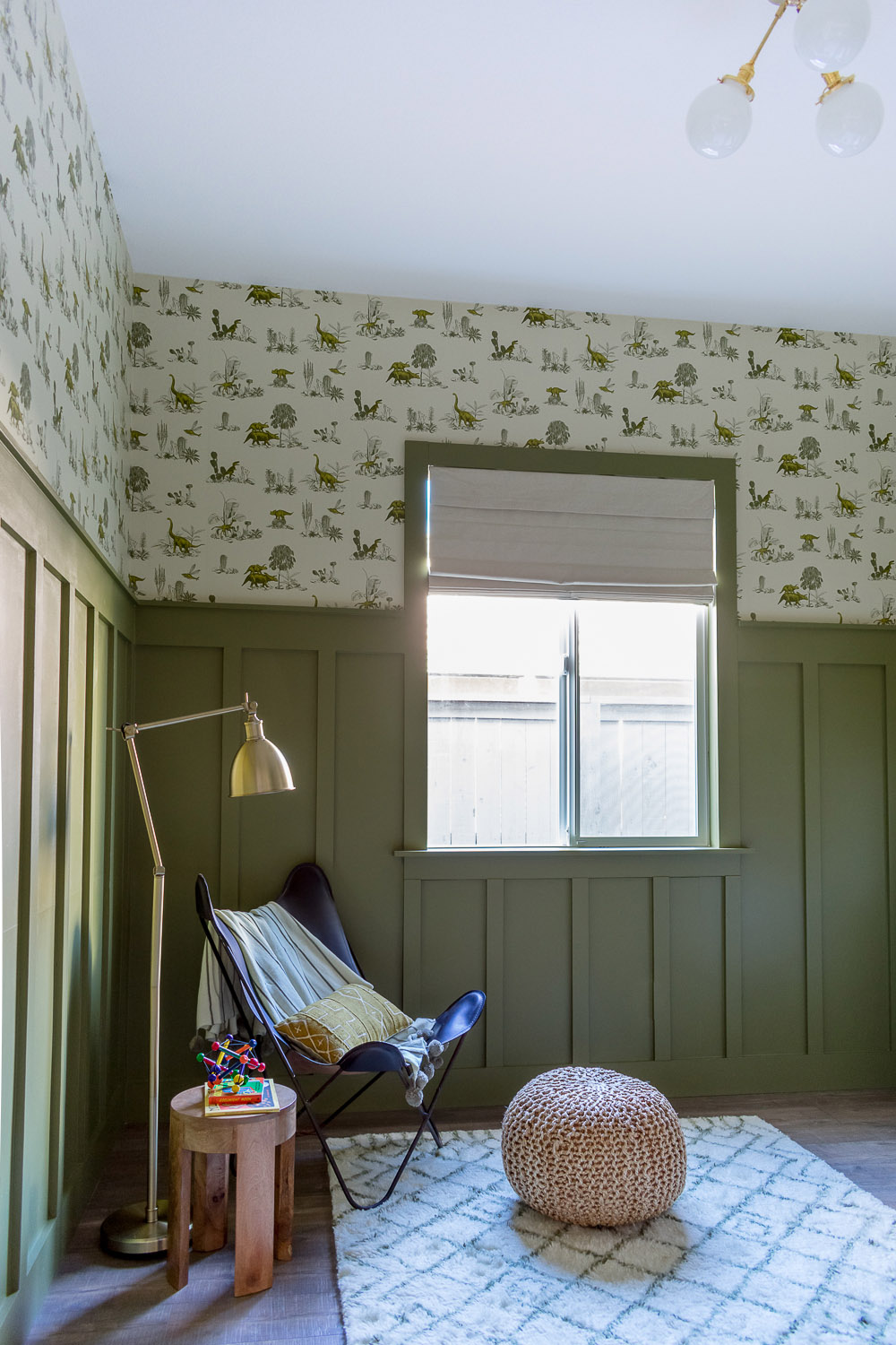 Baby Boy Dinosaur themed nursery will olive green walls, wood paneling, wallpaper, and leather butterfly chair by Beebout Design.