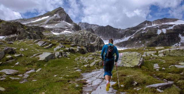 Man hiking through the alps on an eco-tourism adventure
