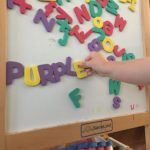 2 year old spelling the word purple using magnet letters on a whiteboard.
