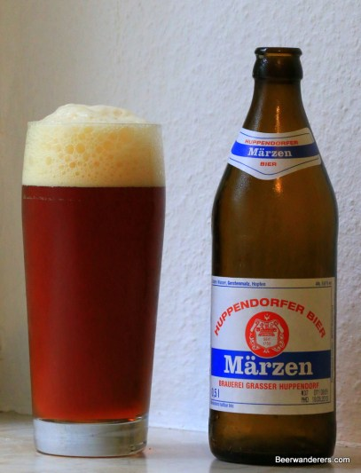 amber beer in glass with bottle