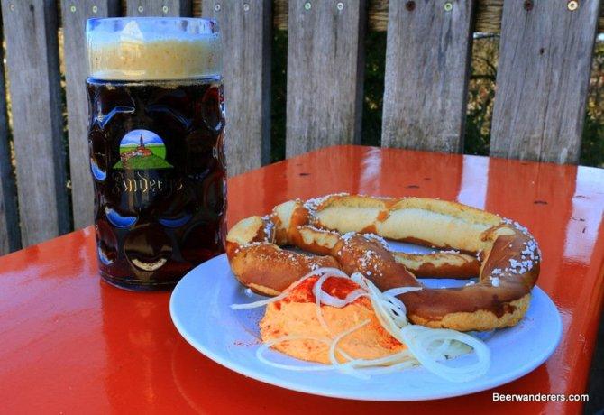 dark beer in mug with big pretzel