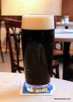black beer with tan head in glass