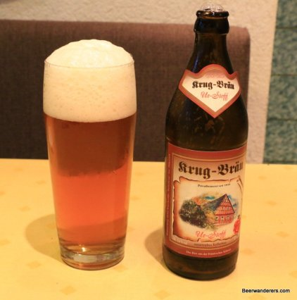 unfiltered light amber beer in glass with bottle