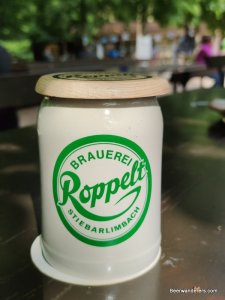 beer in ceramic mug with logo and cover