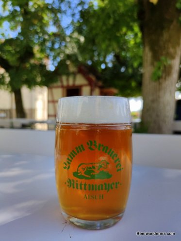 unfiltered amber beer in mug with logo