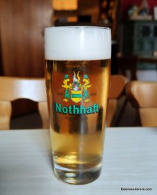 yellow beer in glass with logo