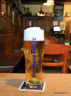 golden beer in glass with big head
