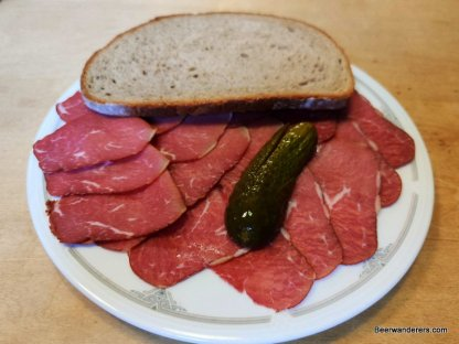 cold cuts on plate with pickle and bread