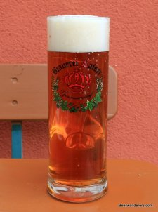 amber beer in tall mug with logo