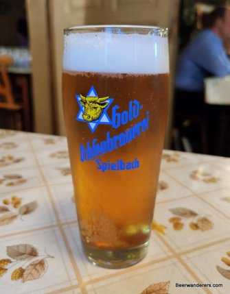 golden beer in glass with logo
