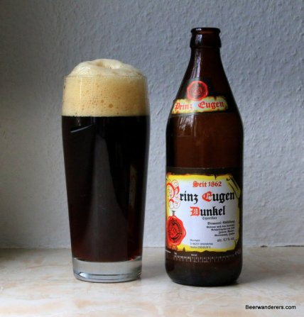 dark beer with massive head in glass with bottle