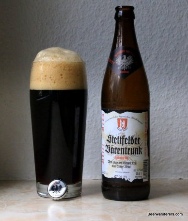 black beer in glass with huge tan head and bottle