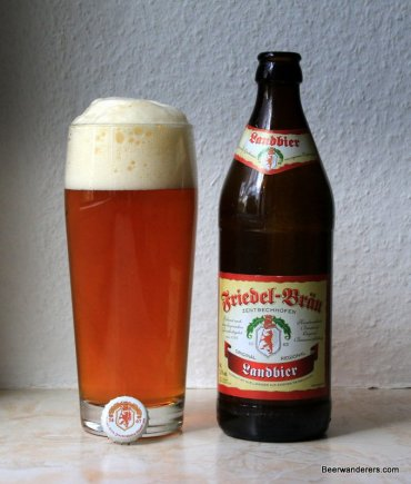 unfiltered amber beer in glass with bottle