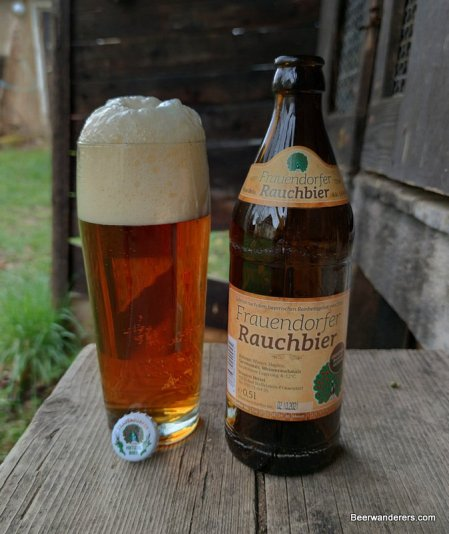 amber beer with huge head in glass with bottle