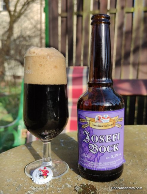 black beer with big tan head in glass with bottle