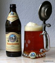 unfilltered amber beer in glass mug with pewter light with bottle