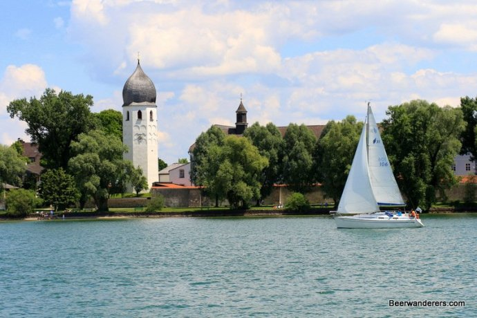 sailboat on lake in front of a church