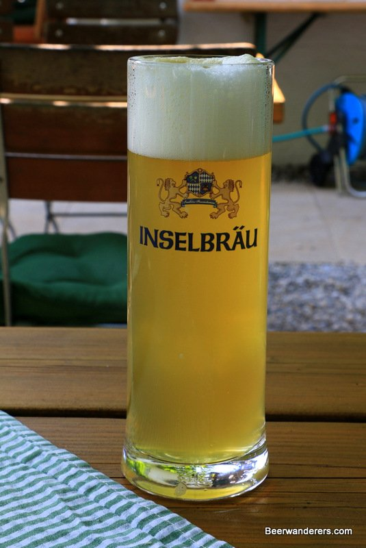 unfiltered yellow beer in logo glass