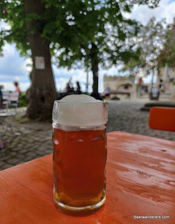 unfiltered amber beer in mug in biergarten