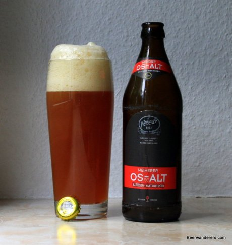 unfiltered amber beer with big head in glass with bottle