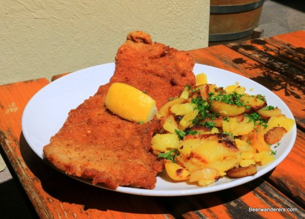 huge schnitzel with fried potatoes and a lemon wedge