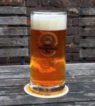 amber beer with big head in logo mug