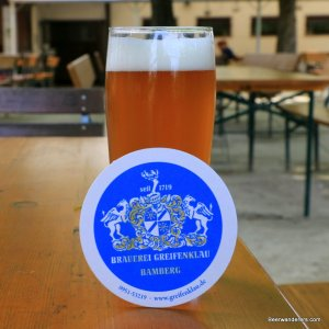 unfiltered golden beer in glass with coaster